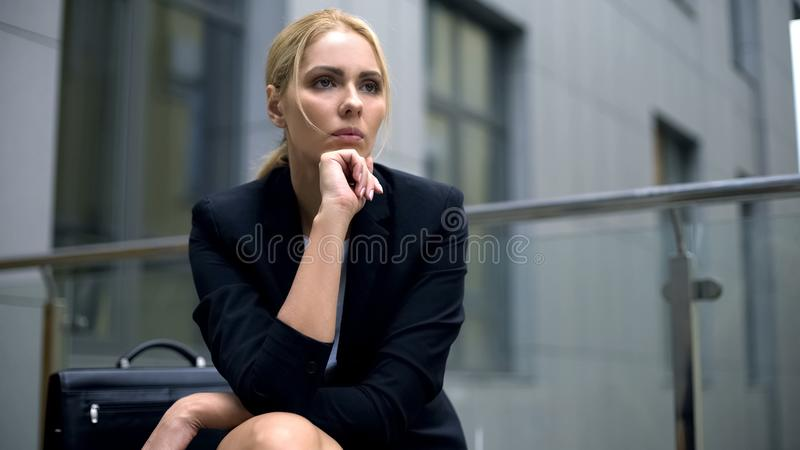 Woman worried about dismissal from work, sitting on bench, feeling depression stock photography