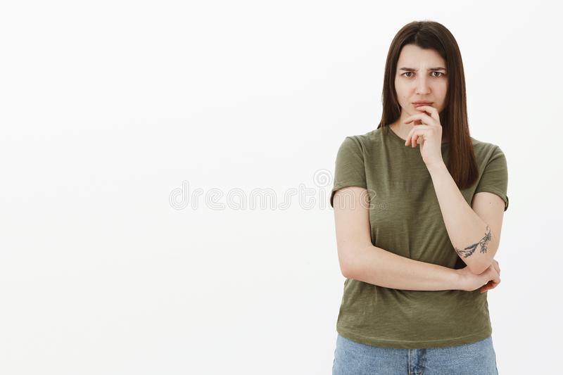 Woman worried and hesitant as hearing something disturbing thinking frowning from worry and intense disapproval holding. Hand on lip, considering what do stock photography
