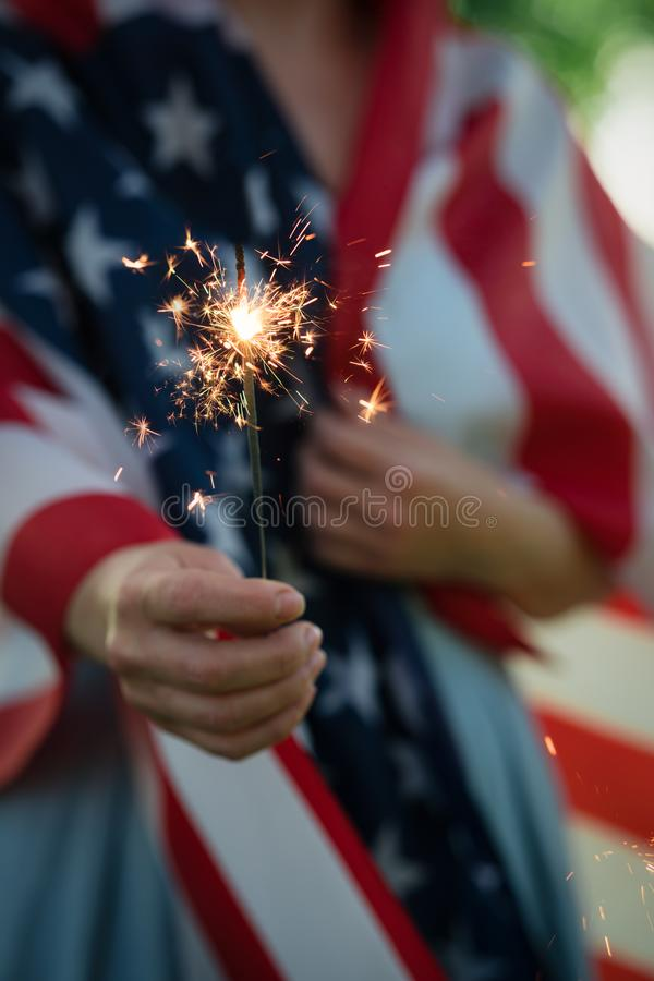 Woman wrapped in American flag standing in the park holding sparkler royalty free stock photos