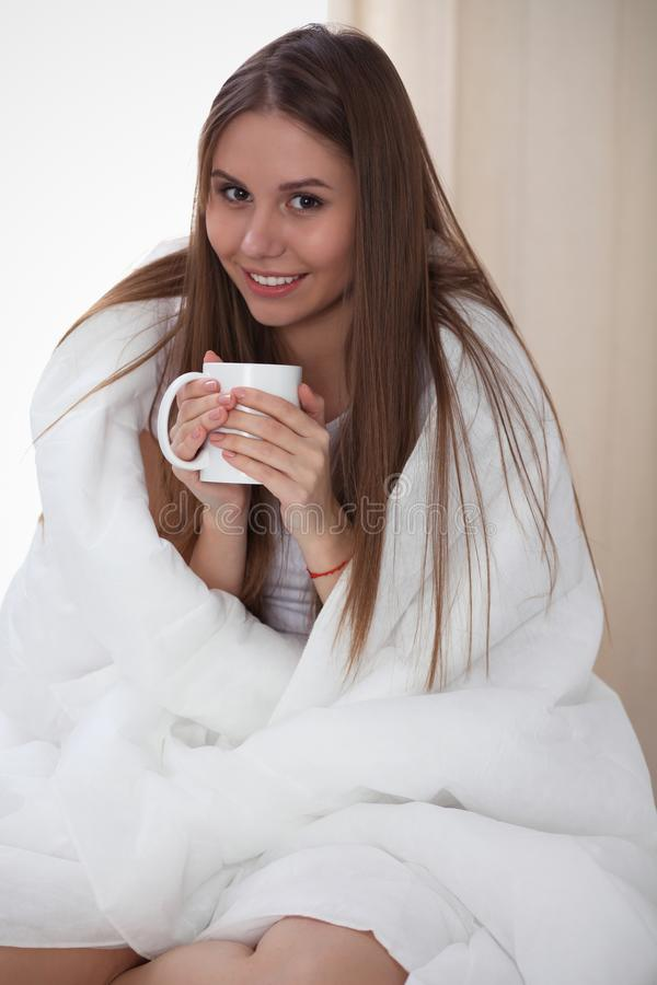 Woman wrapped in a blanket and holds a mug after wake up, entering a day happy and relaxed after good night sleep. Sweet. Dreams, good morning, new day, weekend royalty free stock photos