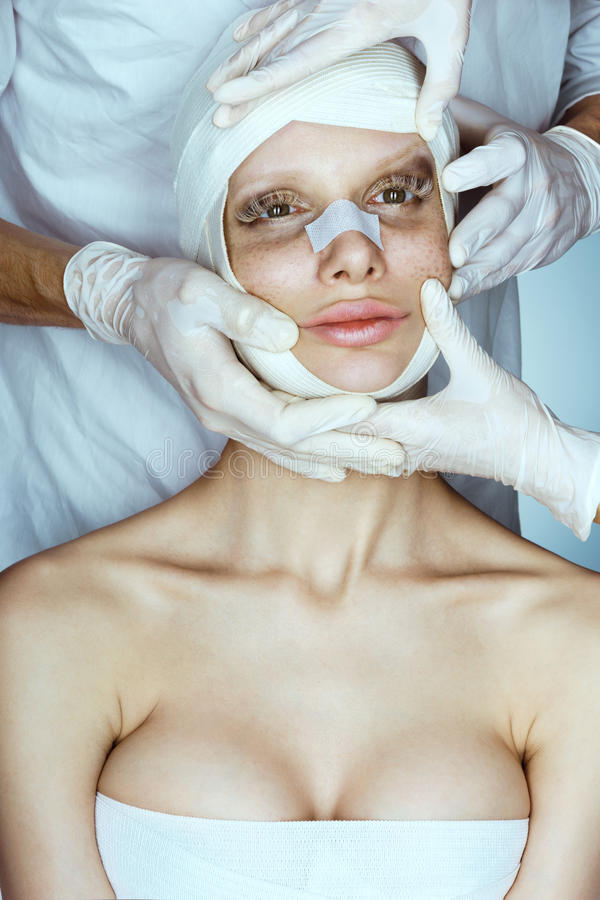 Woman wrapped in medical bandages after facelift. Surgeon or beautician hands touching woman face. Beautiful perfect face stock photo