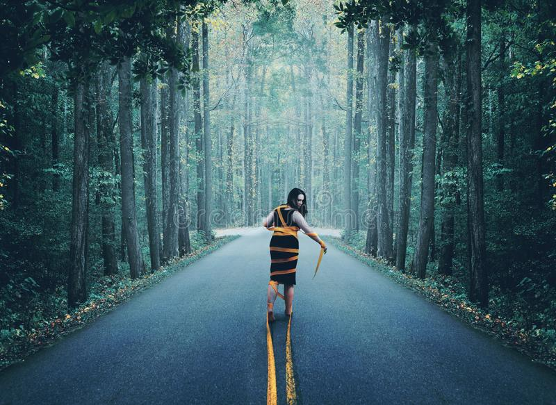 Woman wrapped up in road. A woman wrapped up in the yellow road lines royalty free stock images