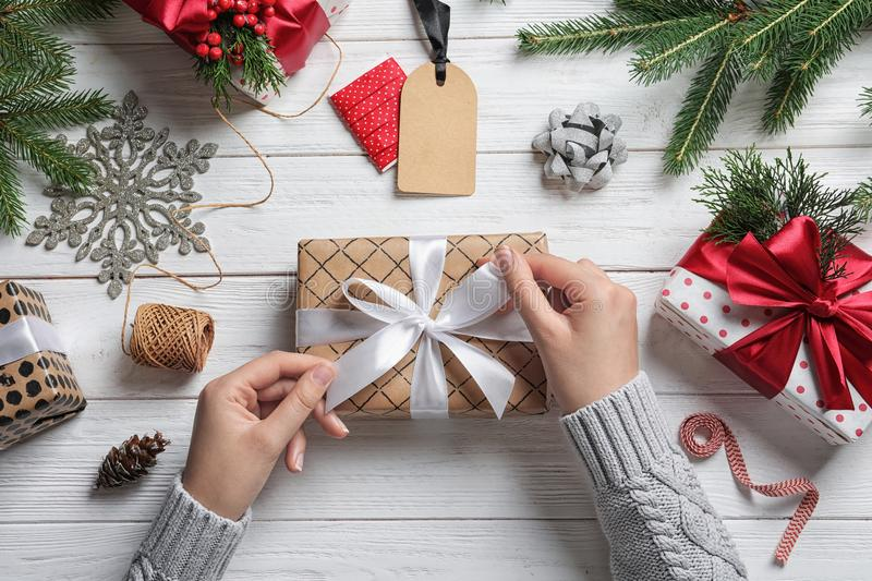 Woman wrapping Christmas gift at wooden table stock images