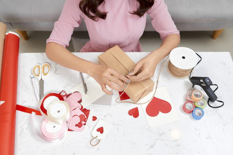 Valentine day theme. Beautiful romantic woman making present for her couple.  stock photography