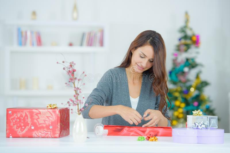 Woman wrapping the gifts stock photo