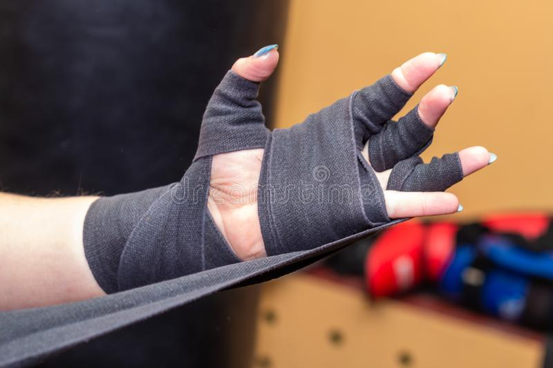 Woman is wrapping hands with grey boxing wraps. Closeup royalty free stock photos