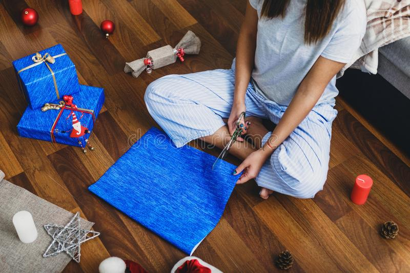 Woman wraps Christmas gifts sitting at home on floor stock image