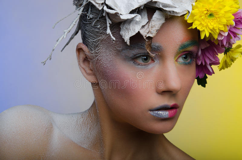 Woman in a wreath of flowers. Beauty in a wreath live and dead flowers stock photo