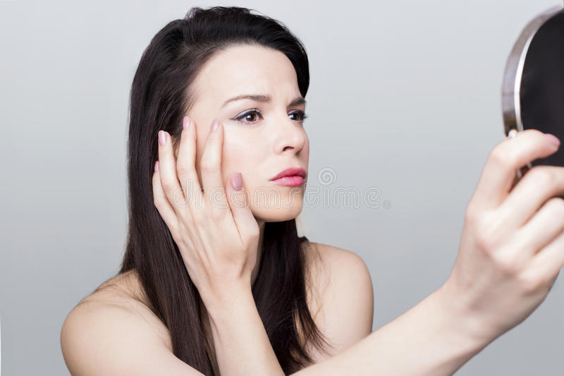 Woman wrinkles. Beautiful woman checking her wrinkles royalty free stock photos