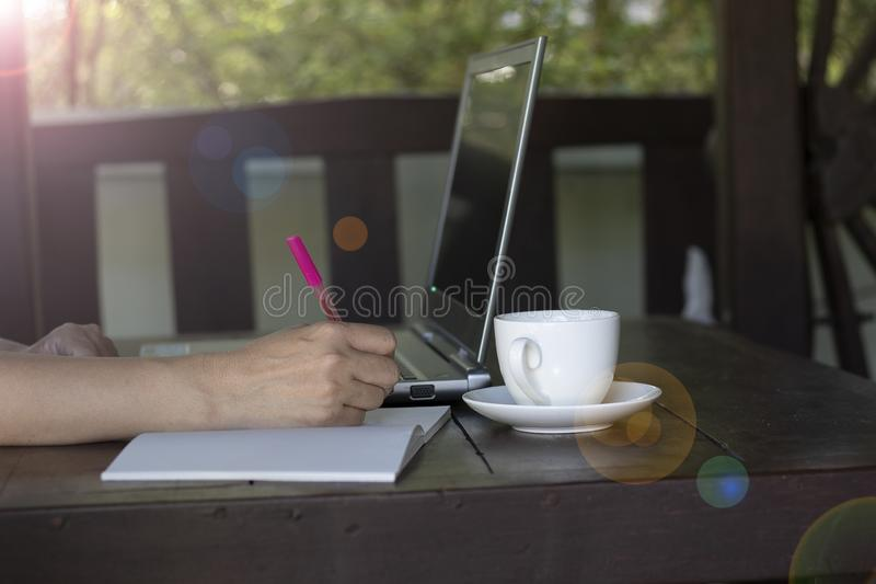 A woman write note on notebook and open laptop with coffee cup on wooden table royalty free stock photography