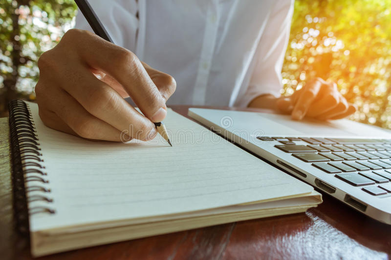 Woman write on notebook and use laptop vintage tone. stock images