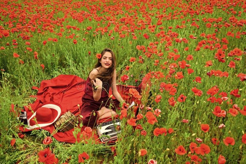 Woman writer in poppy flower field. royalty free stock photo