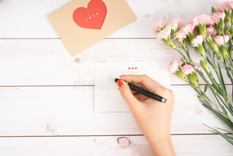 Woman writes love letter on white paper with red heart shape figures.Hand made postcard for Saint Valentines Day celebration.Send stock image