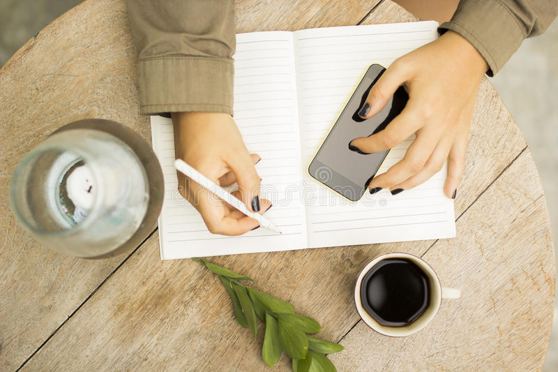 Woman writes in notebook with cell phone and cup of coffee stock images