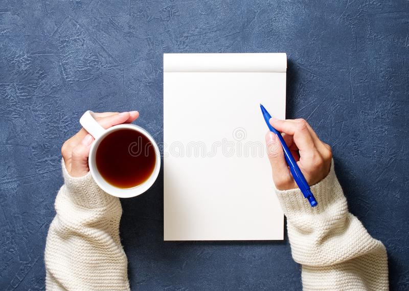 Woman writes in notebook on dark blue table, hand in shirt holding a pencil, cup of tea, sketchbook drawing, top view. Woman writes in notebook on a dark blue stock photography