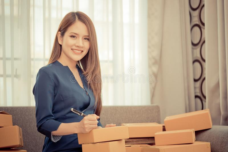 Woman writing address and sending package for online business royalty free stock photo