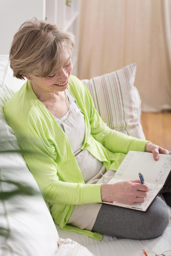 Woman writing in agenda stock photos