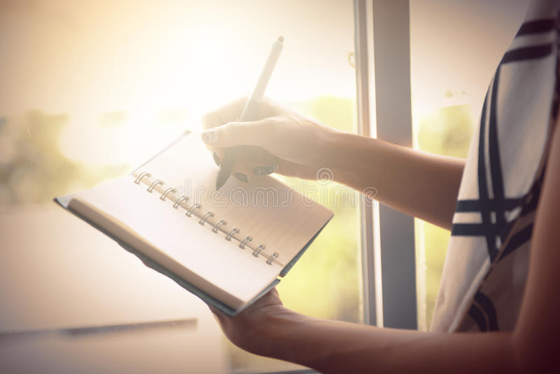 Woman writing on blank notebook on bed in the morning. royalty free stock photography