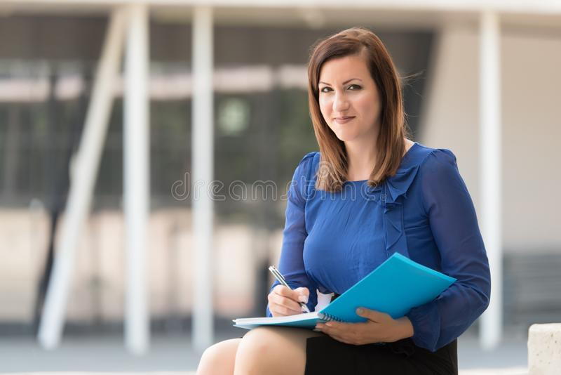 Woman writing on in a blue book stock photography