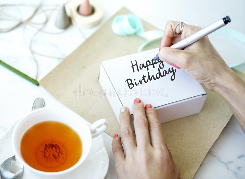 Woman writing Happy Birthday on a white box stock images