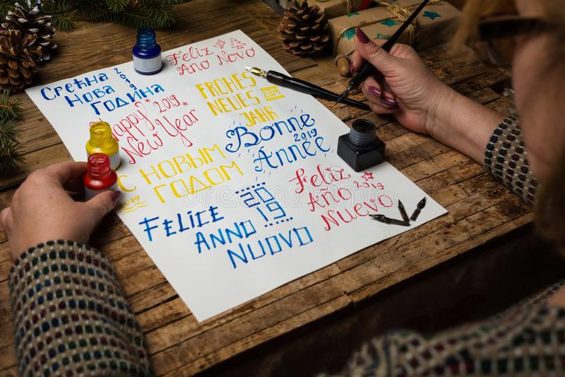 Woman writing happy new year in different languages. Woman writing happy new year in many different languages calligraphy royalty free stock image