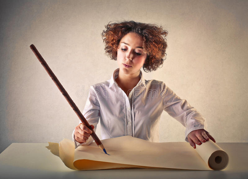 Woman writing with a huge pencil royalty free stock photography