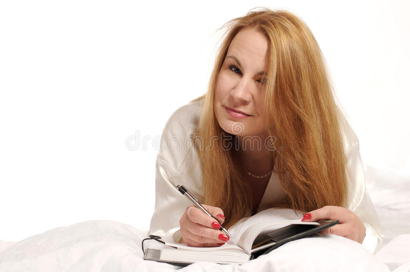 Woman writing in journal stock photography
