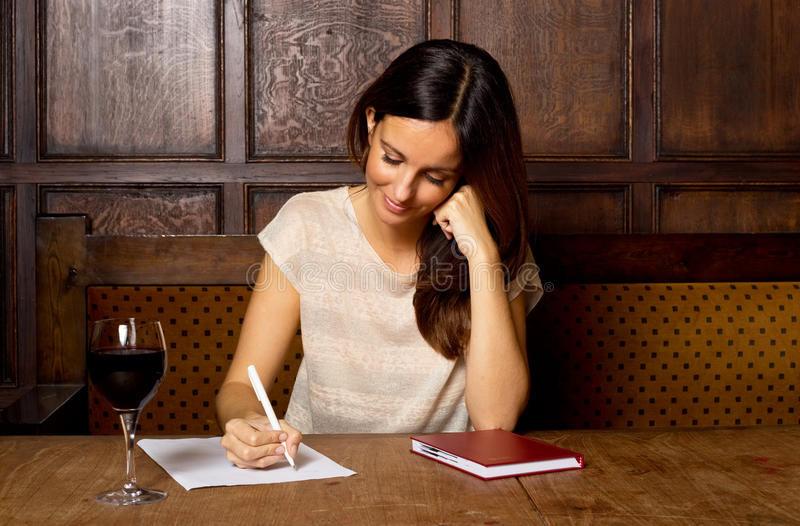 Woman writing a letter in a bar. Young woman writing with a glass of wine royalty free stock photography