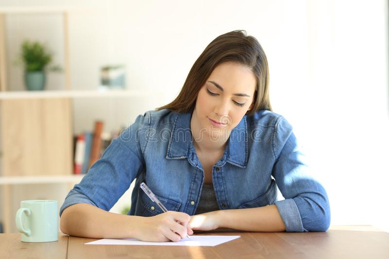 Woman writing a letter on a table at home. Front view portrait of a serious woman writing a letter on a table at home stock image