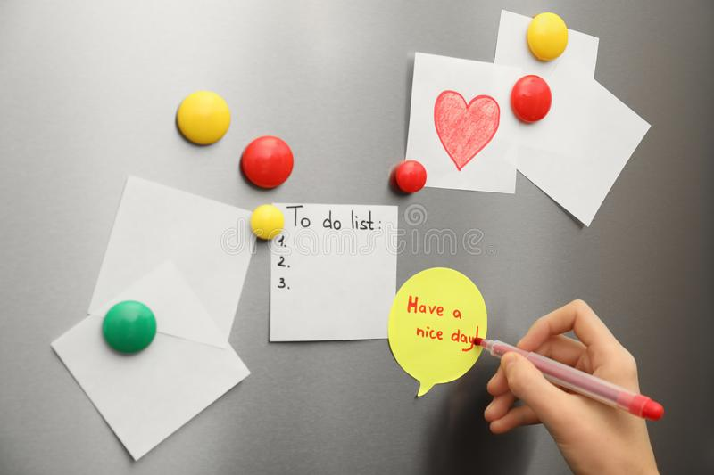 Woman writing message on note stuck to refrigerator door stock photo