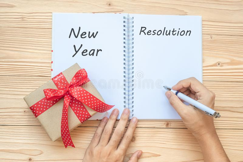 Woman writing 2019 New Year Resolutions word with notebook and Christmas decoration on wooden table, Top view and copy space. Goal royalty free stock photo