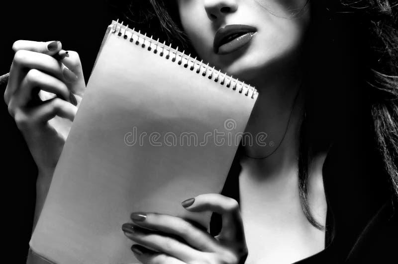 Woman writing a note. B&w stock photo