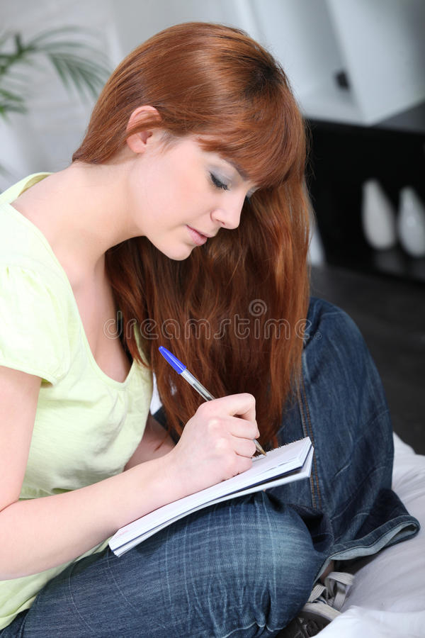 Woman writing in a notebook stock images