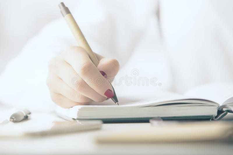 Woman writing in notepad. Close up of woman`s hand writing in notepad placed on desktop with other items stock photo