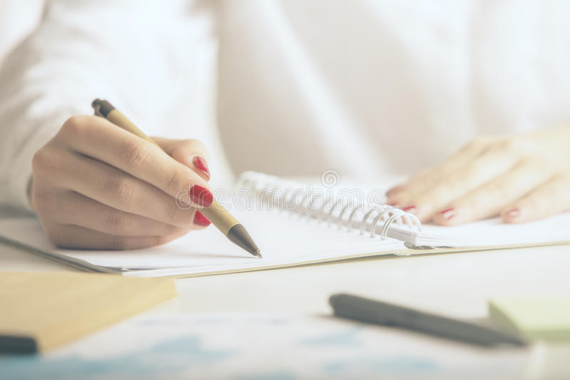 Woman writing in notepad. Woman writing in spiral notepad placed on desktop with other items. Close up stock photos