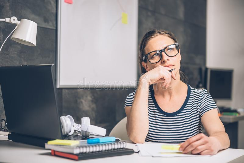 Woman writing notes and contemplating at the office. Woman wearing eyeglasses writing notes and contemplating at the office stock images