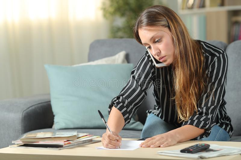 Woman writing notes talking on phone at home. Woman writing notes talking on mobile phone sitting on a couch in the living room at home royalty free stock photo