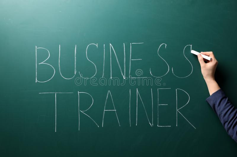 Woman writing text BUSINESS TRAINER royalty free stock image