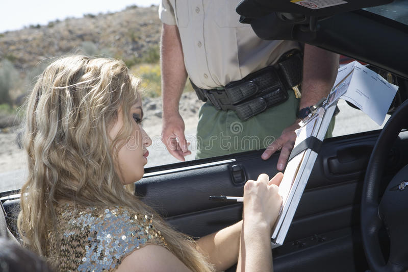 Woman Writing On Traffic Ticket stock image