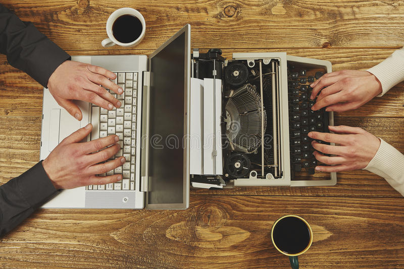 Woman writing on a typewriter and a man working on a laptop.Closeup to hands.Technological evolution. stock photo