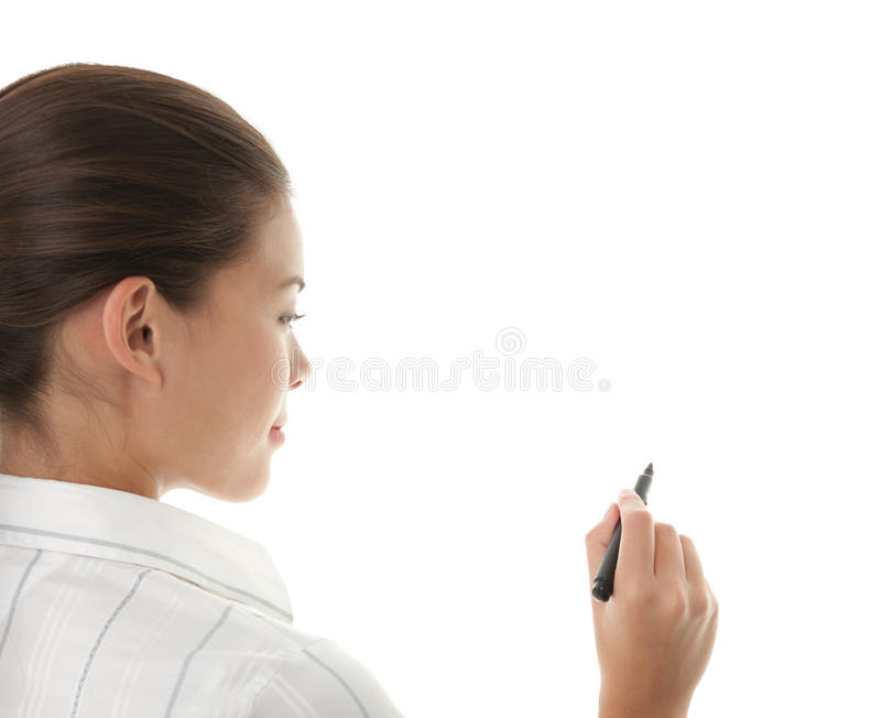 Woman writing on whiteboard. Writing with pen. Young beautiful businesswoman with pen writing on whiteboard. Focus on the black marker - lot's of copy space royalty free stock image