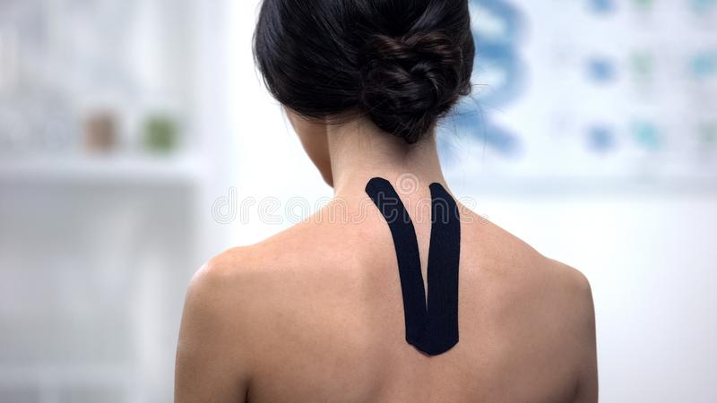 Woman with Y-shaped tape on upper back, reducing pain, alternative medicine stock image