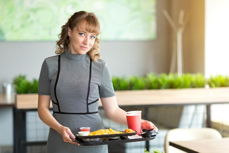 Young woman with a tray of food in a cafe. stock images