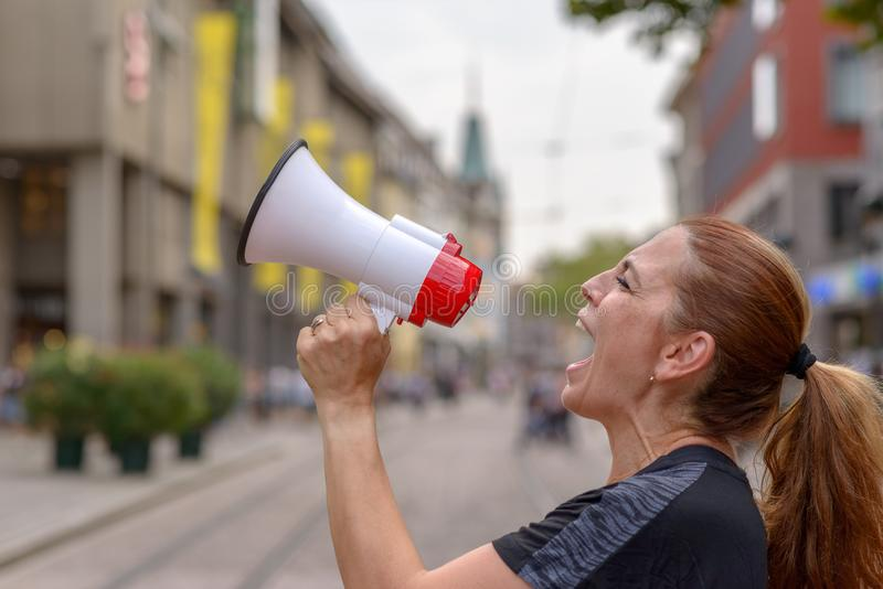 Woman yelling into a bullhorn. On an urban street voicing her displaeasure during a protest or demonstration close up side view of her face royalty free stock images