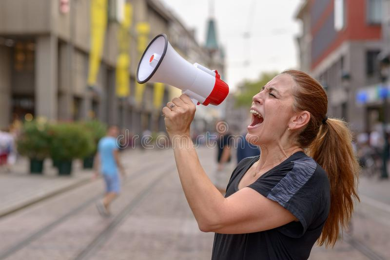 Woman yelling into a bullhorn. On an urban street voicing her displaeasure during a protest or demonstration close up side view of her face royalty free stock photos