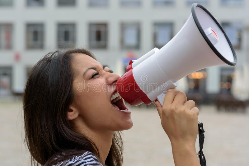 Woman yelling into a bullhorn on an urban street. Voicing her displaeasure during a protest or demonstration, close up side view of her face royalty free stock photography