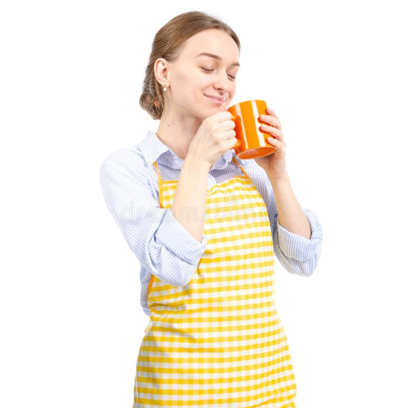 Woman in yellow apron orange cup in hand royalty free stock photos