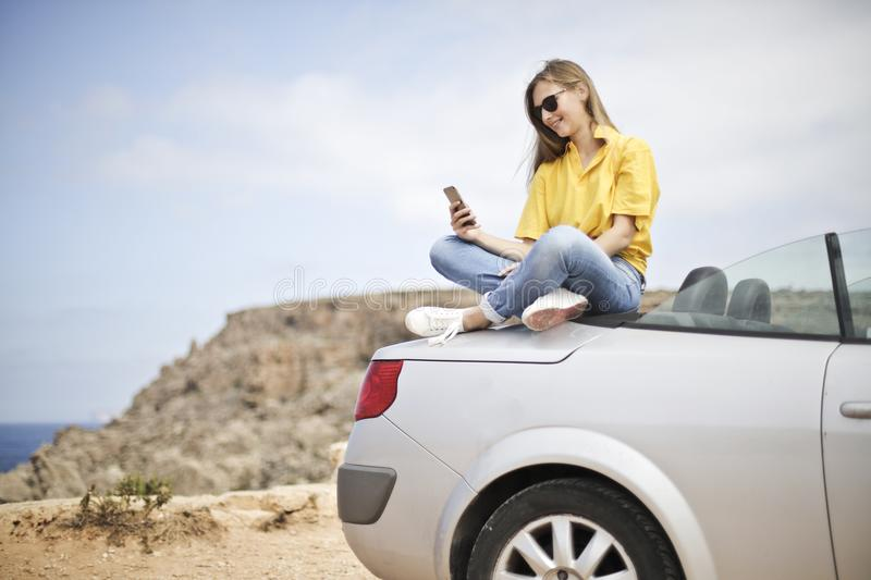 Woman in Yellow Blouse and Blue Jeans Taking Selfie While Sitting on Car royalty free stock photos