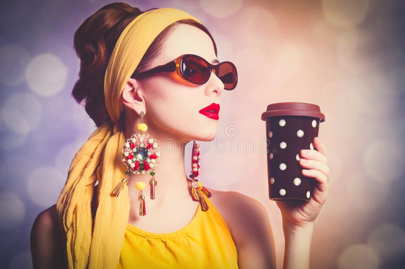 Woman in yellow clothes with coffee stock image