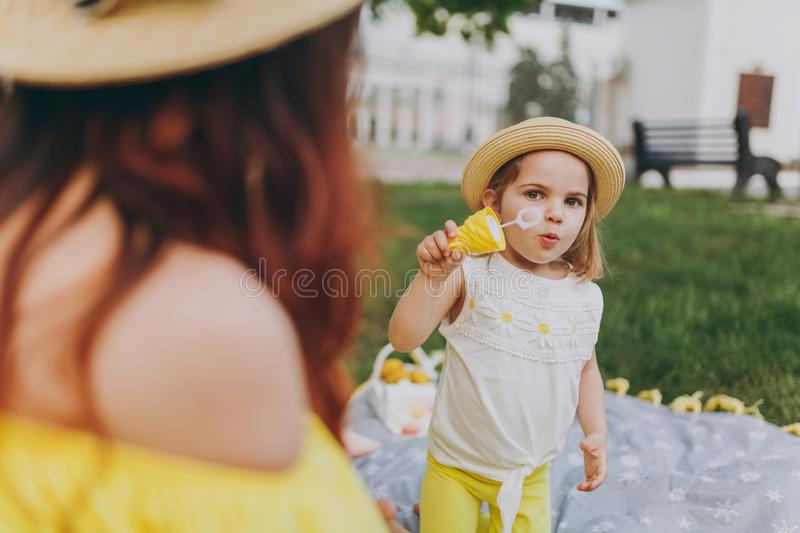 Woman in yellow clothes play on grass in park rest, amuse with little cute child baby girl blowing soap bubbles. Mother stock photos